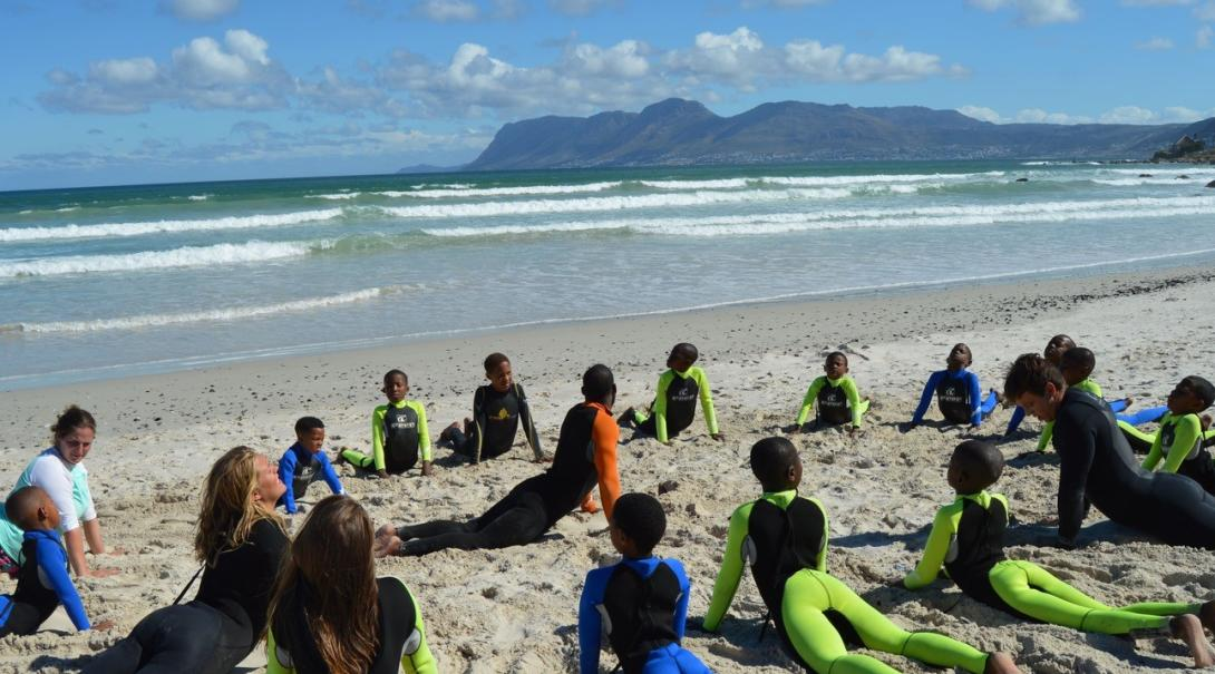 Projects Abroad volunteers stretching on the beach with children and gaining new skills at a Surfing Project